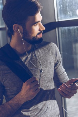 Photo for Portrait of man listening music in earphones and looking out window - Royalty Free Image