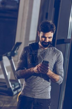 Photo for Portrait of man listening music in earphones in gym - Royalty Free Image