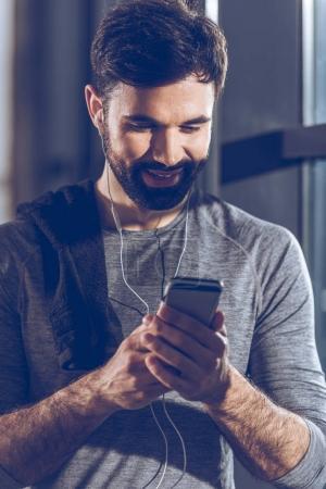 Photo pour Portrait de l'homme écoutant de la musique dans les écouteurs après la formation - image libre de droit