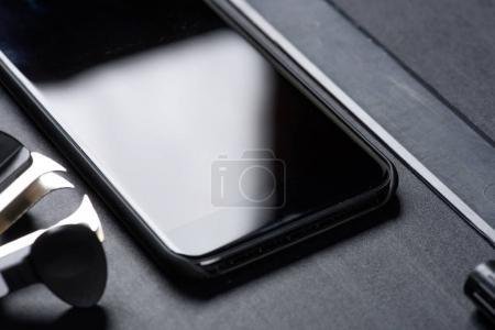 Photo for Close up of smartphone with ruler and office supplies isolated on black - Royalty Free Image