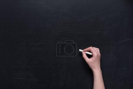human hand writing on chalkboard