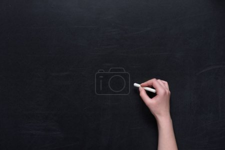 Photo for Human hand writing with piece of chalk on black chalkboard - Royalty Free Image