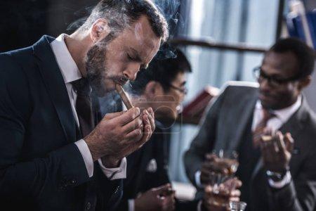 Photo pour Cigare fumer homme d'affaires avec l'équipe des affaires multiculturelles, passer du temps derrière - image libre de droit