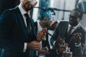 """Постер, картина, фотообои """"Бизнесмен курение сигары с многокультурной бизнес-команды тратят время за"""""""