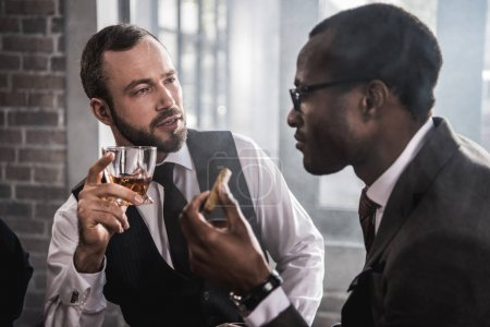 Two confident men with cigar and glass of alcohol beverage talking