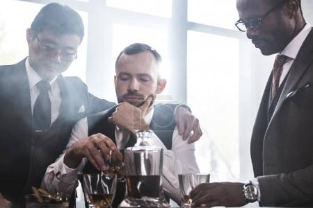 Multiethnic group of businessmen smoking and drinking whisky indoors, business team meeting