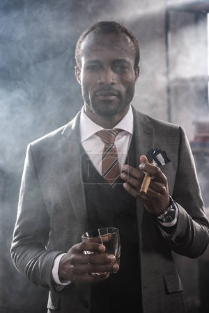 Confident african american businessman holding glass with whiskey and smoking cigar