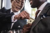 Cropped shot of two smiling businessmen talking and holding dollar banknote