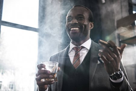 Smiling african american businessman holding glass with whiskey and smoking cigar