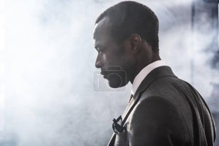 Profile portrait of confident african american businessman in suit looking away