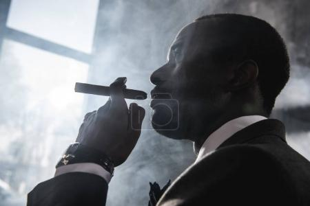 Side view of confident african american man smoking cigar indoors