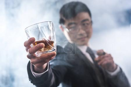 Close-up view of confident asian businessman drinking whiskey and smoking cigar