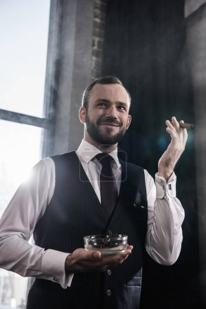Portrait of handsome smiling bearded man holding ashtray and smoking cigar indoors
