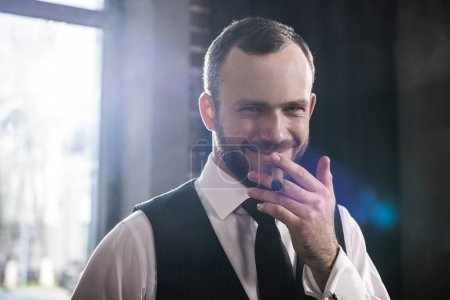 Close-up portrait of handsome smiling confident man smoking cigar indoors
