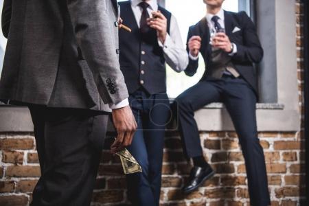 Photo pour Plan recadré d'un homme d'affaires tenant un billet en dollar et regardant ses collègues boire du whisky, réunion de l'équipe d'affaires - image libre de droit