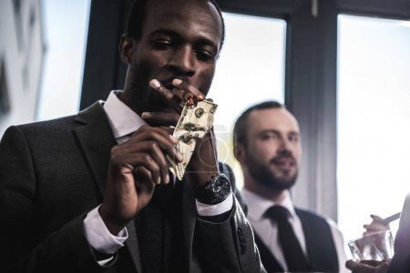 Confident businessman lighting cigar with dollar banknote indoors
