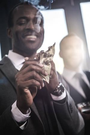 Close-up view of confident smiling businessman lighting cigar with dollar banknote