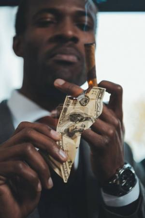 confident african american businessman smoking cigar and burning dollar banknote