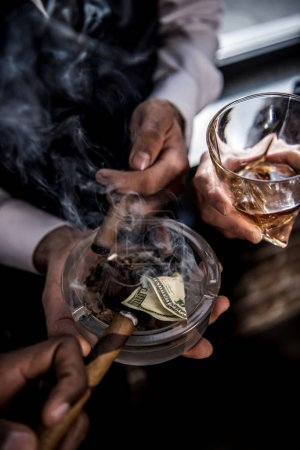 Close-up partial view of businessmen with dollar banknote in ashtray drinking whiskey and smoking cigars