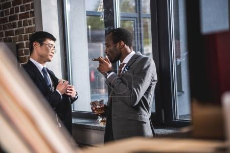Confident businessman drinking alcohol beverage and smoking cigar while colleague hiding money into suit pocket, business team meeting
