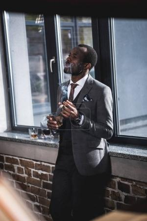 Confident businessman holding glass with whiskey and smoking cigar indoors