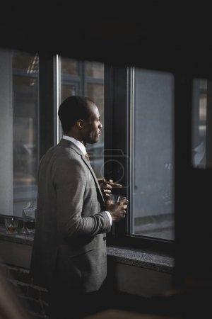 Photo pour Songeur africain-américain homme d'affaires en costume avec verre de cigare fumer whisky - image libre de droit