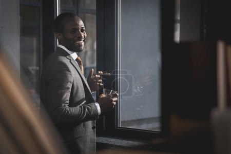 smiling african american businessman in suit with glass of whiskey smoking cigar
