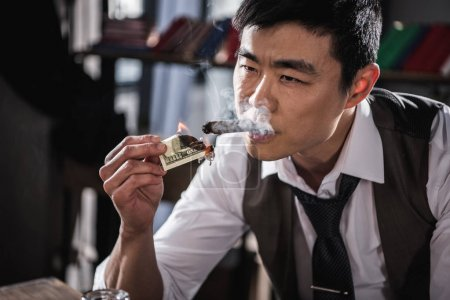 Portrait of confident businessman smoking cigar with money in hand