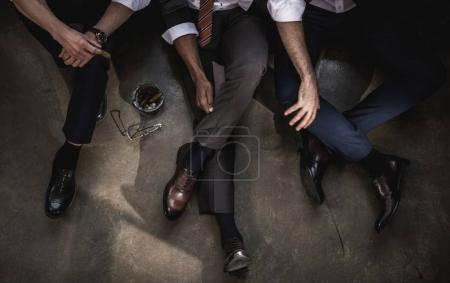 Cropped shot of group of businessmen sitting on floor together