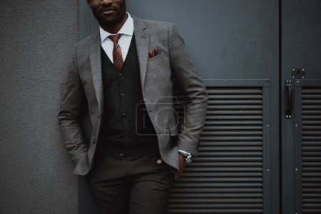 confident stylish african american businessman posing outdoors at wall