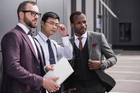 Photo pour Portrait d'une équipe d'affaires multiculturelle confiante debout près du bureau et regardant de côté - image libre de droit