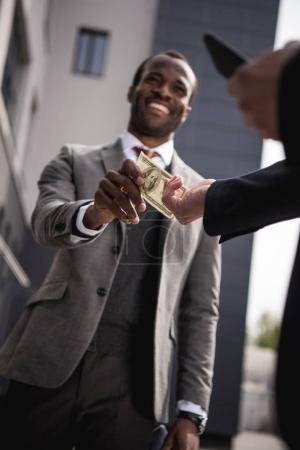 Photo pour Jeune homme d'affaires américain en vetu en prenant l'argent à l'extérieur - image libre de droit