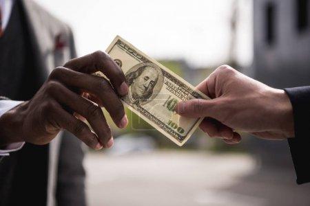 Photo pour Mains d'hommes d'affaires anonyme détenant des billets de cent dollars à l'extérieur - image libre de droit