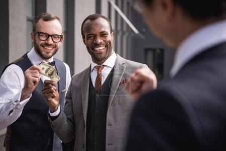 Photo pour Jeunes hommes d'affaires multiethniques souriants en tenue de cérémonie se réunissant à l'extérieur, réunion d'équipe d'affaires - image libre de droit