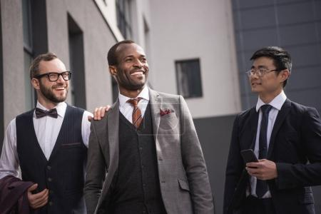 Photo pour Jeunes hommes d'affaires multiethniques élégants en tenue de cérémonie marchant à l'extérieur, réunion de l'équipe d'affaires - image libre de droit