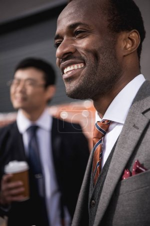 Photo for Young smiling multiethnic businessmen meeting at coffee break outdoors, business team meeting - Royalty Free Image