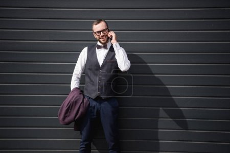young caucasian businessman talking on smartphone while standing outdoors