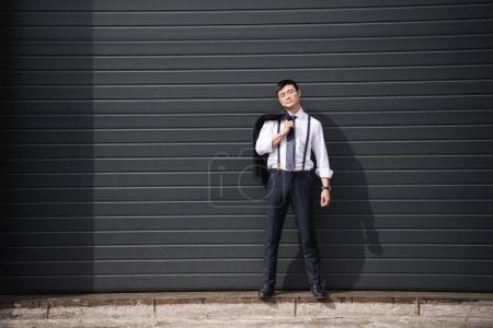 Foto de Joven empresario asiático confidente permanente al aire libre con espacio de copia - Imagen libre de derechos