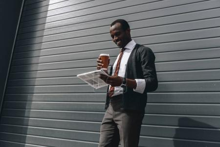 Stylish african american businessman reading newspaper and holding coffee to go outdoors