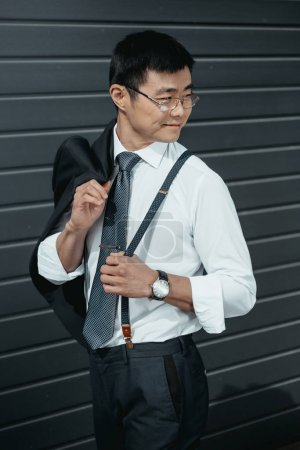 Photo for Confident stylish asian businessman posing outdoors at wall - Royalty Free Image