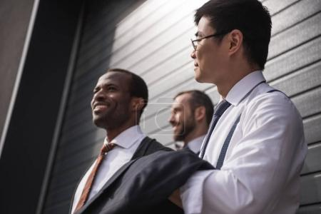 young stylish multiethnic businessmen in formalwear standing outdoors, business team meeting