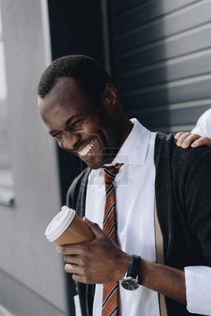 stylish african american businessman laughing and holding coffee to go outdoors