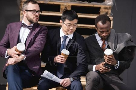 young multiethnic businessmen in formalwear sitting at coffee break outdoors, business team meeting