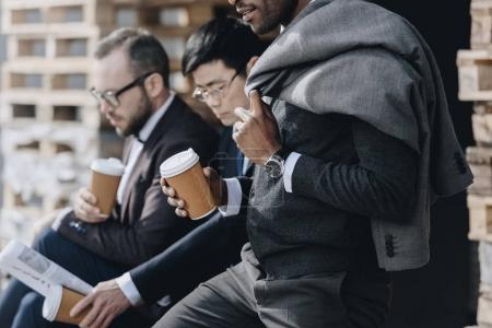 Photo for Multicultural businessmen holding paper coffee cups and sitting outdoors, business people team concept - Royalty Free Image