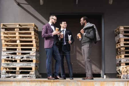 young multiethnic businessmen in formalwear meeting at coffee break outdoors, business team meeting