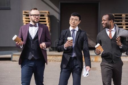 Photo pour Jeunes hommes d'affaires multiethniques en tenue de cérémonie marchant à la pause café en plein air, réunion de l'équipe d'affaires - image libre de droit