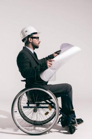 Photo pour Ingénieur concentré dans un casque assis en fauteuil roulant et en regardant plan isolé sur fond gris - image libre de droit
