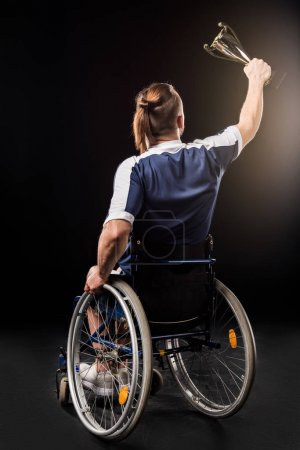 paralympic in wheelchair with trophy