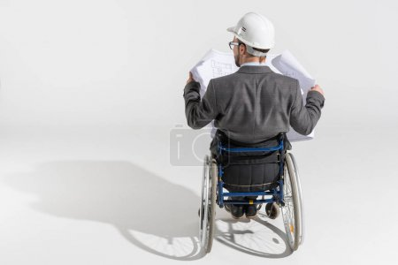 Photo for Disabled architect in wheelchair looking at blueprint isolated on white - Royalty Free Image