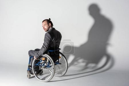 Photo for Young physically handicapped businessman in wheelchair with his shadow on wall - Royalty Free Image